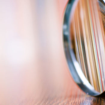 34105449 - close up single magnifying glass with black handle, leaning on the wooden table at the office.